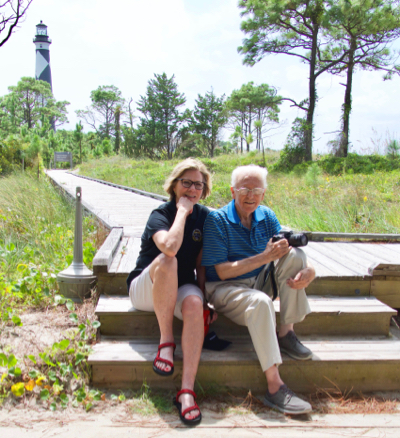 authors Cheryl Shelton-Roberts and Bruce Roberts sit at the end of a boardwalk with a lighthouse in the distance behind them